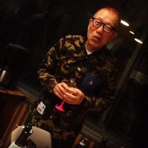 グラスを両手でもつ小林克也さんの写真